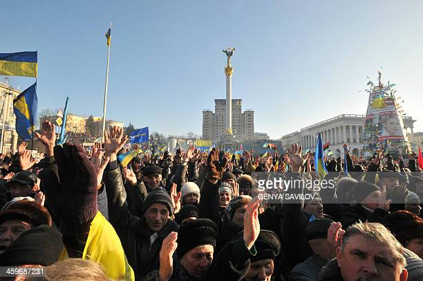 Ukrainian opposition supporters raise their hands during a mass rally on Independence Square in Kiev on December 29 2013 Tens of thousands of irate...
