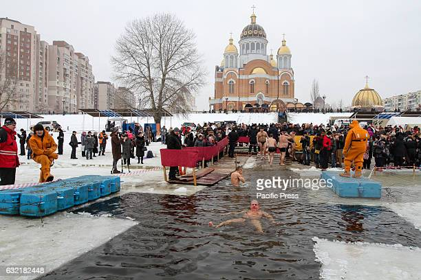 Ukrainian Orthodox believers bathe in crossalike iceholes on Dnipro river as they celebrate Epiphany