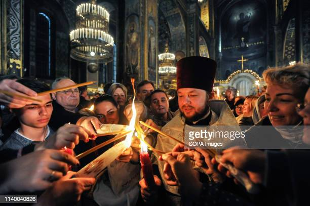Ukrainian Orthodox faithful are seen lighting candles from the Holy Fire brought from Jerusalem at St Volodymyr Cathedral during the ceremony of the...