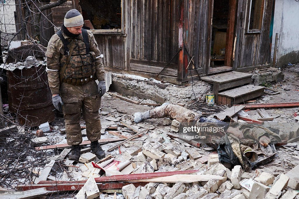 A Ukrainian paramilitary is found dead by pro-Russian rebels outside a damaged house on February 7, 2015 in Uglegorsk, Ukraine. According to Pro-Russian rebels, control of Uglegorsk, on the frontline near Debaltseve, was regained two days ago, after eight days of fierce fighting.