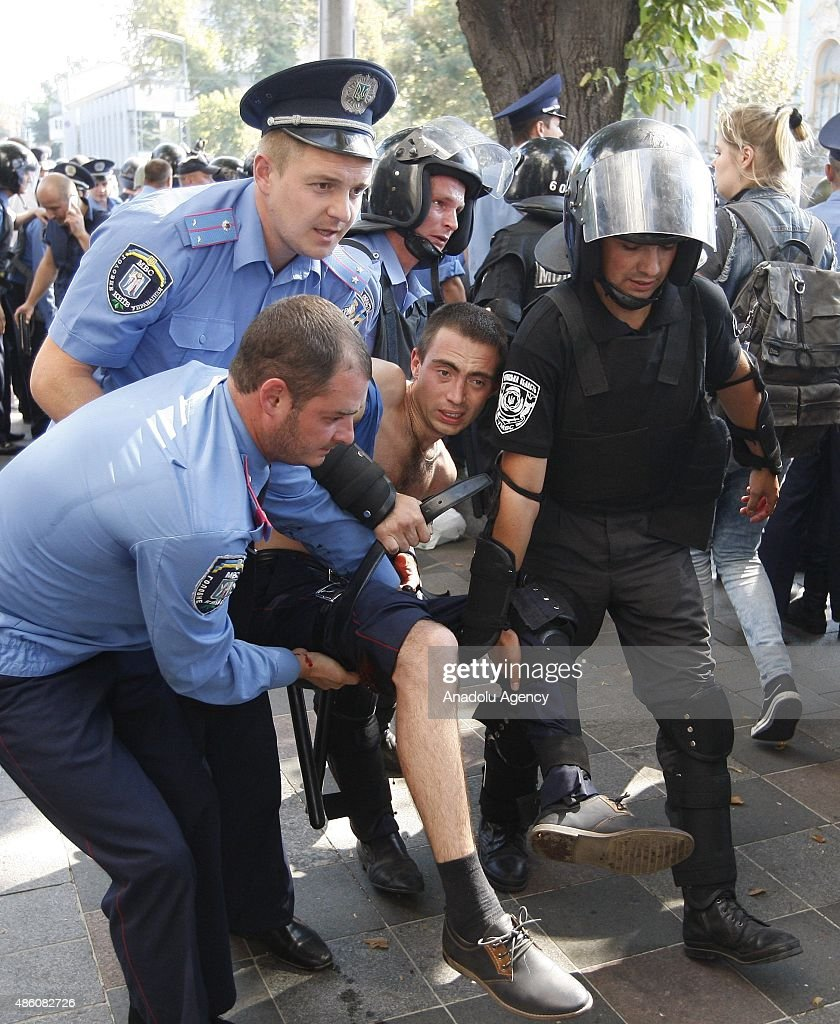 Ukrainian police carry their colleagues wounded in clashes broken out between police and protesters outside the Ukrainian parliament in Kiev on August 31, 2015 after vote to provide greater powers to separatist regions in the east. At least 50 were wounded in clashes outside parliament in Kiev on Monday after lawmakers made constitutional changes granting more autonomy to pro-Russian separatists in eastern Ukraine.