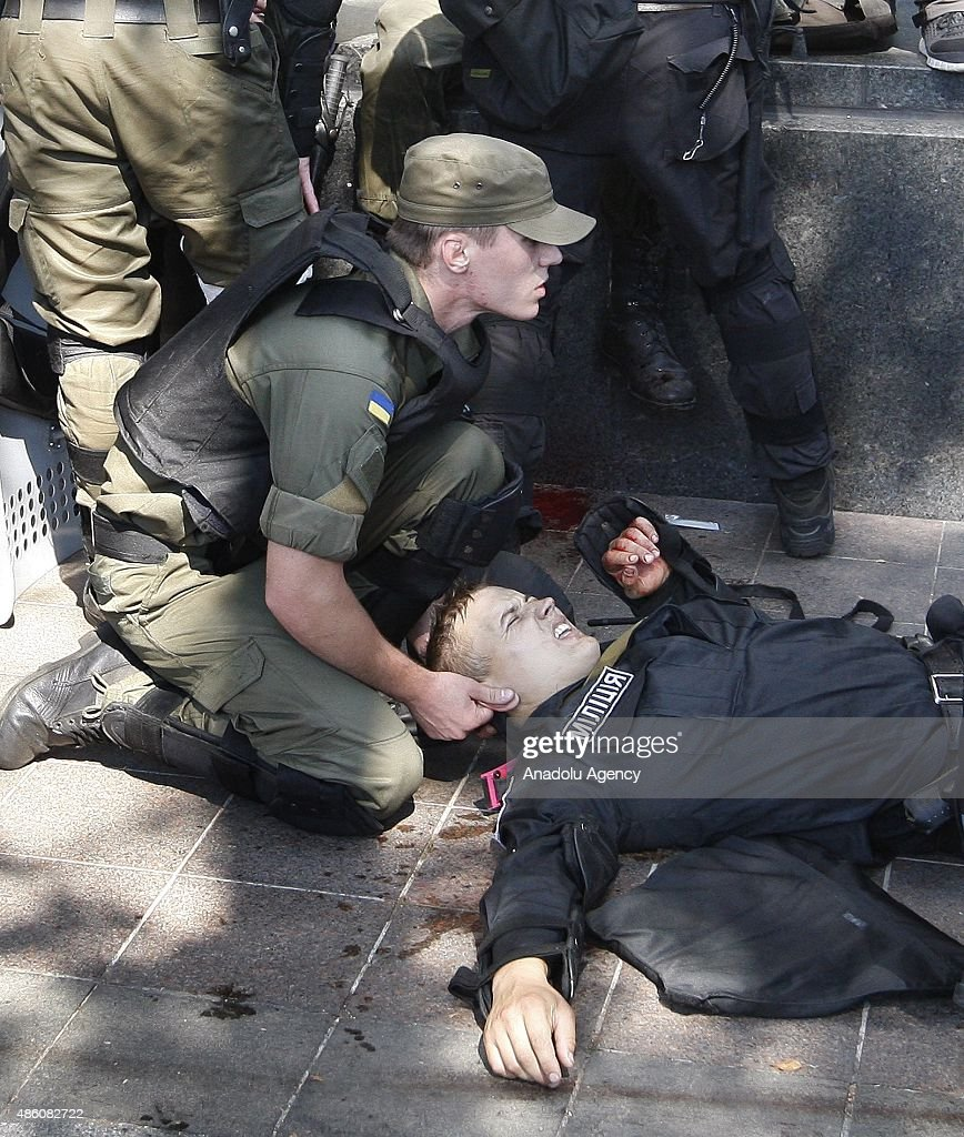 Ukrainian police help their colleagues wounded in clashes broken out between police and protesters outside the Ukrainian parliament in Kiev on August 31, 2015 after vote to provide greater powers to separatist regions in the east. At least 50 were wounded in clashes outside parliament in Kiev on Monday after lawmakers made constitutional changes granting more autonomy to pro-Russian separatists in eastern Ukraine.