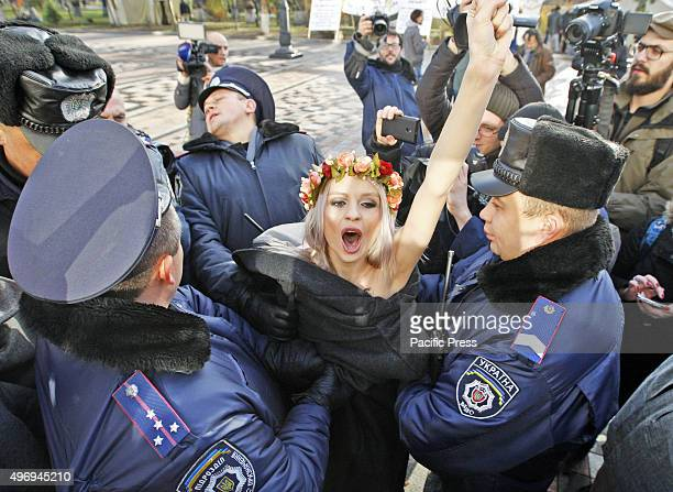 Ukrainian policemen detain activists of the women movement FEMEN during their topless protest Stop Homophobia in front of Parliament building The...