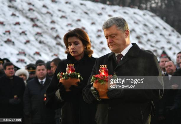 Ukrainian President Petro Poroshenko and his wife Maryna Poroshenko hold symbolic bowls with wheat and candles as theytake part in a commemoration...