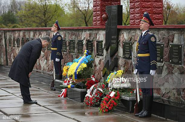 Ukrainian President Petro Poroshenko bows after placing flowers at a memorial to plant workers who died as a result of the Chernobyl nuclear accident...