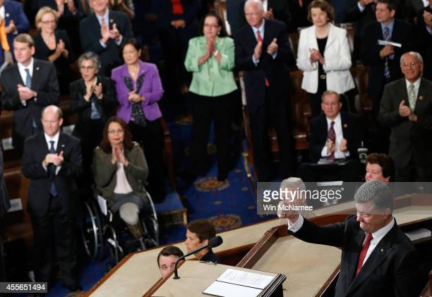 Ukrainian President Petro Poroshenko gives a thumbs up sign as he is applauded by members of the US Congress while addressing a joint meeting of the...