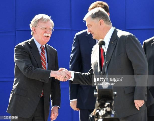 Ukrainian President Petro Poroshenko shakes hand with US National Security Advisor John Bolton during a military parade in Kiev on August 24 to...
