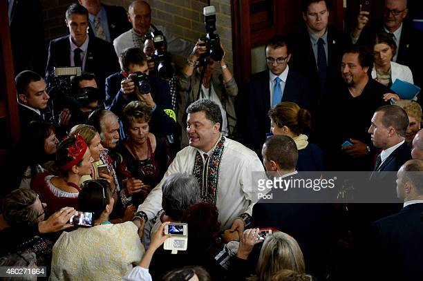 Ukrainian President Petro Poroshenko shakes hands with the crowd as he leaves in a traditional shirt with his wife Maryna after an ecumenical church...