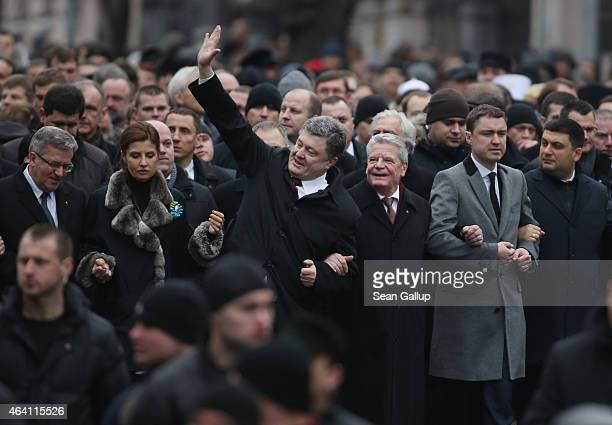 Ukrainian President Petro Poroshenko waves as he walks arm in arm with German President Joachim Gauck in the 'March of Diginity' prior to ceremonies...