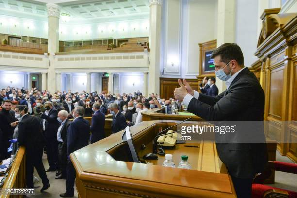 Ukrainian President Volodymyr Zelensky, wearing a face mask, reacts after lawmakers voted adopted a new land reform at the parliament in Kiev on...