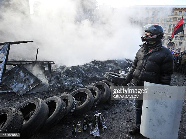A Ukrainian protester wearing a helmet and holding a makeshift shield stands next to a pile of burning tyres in central Kiev on January 23 2014...