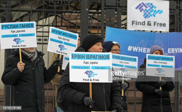Ukrainian protesters are seen holding placards during the protest. Protesters held placards with the names of missing Crimean activists during the...