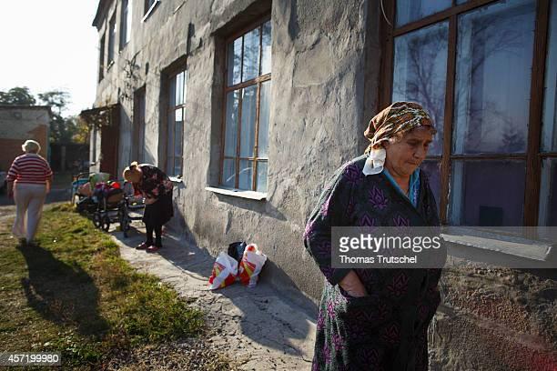 Ukrainian refugees stand outside refugee accommodations in on October 14 2014 in Kharkiv Ukraine German Development Minister Gerd Mueller is on a...