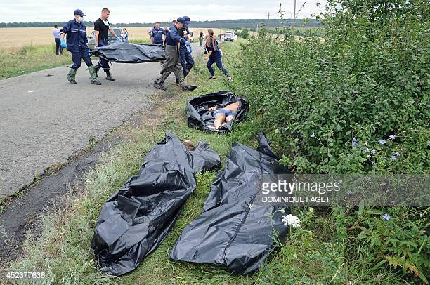 Ukrainian rescue workers carry the body of a victim on a stretcher as others bodies of victims lay on the ground prior to be collected at the site of...