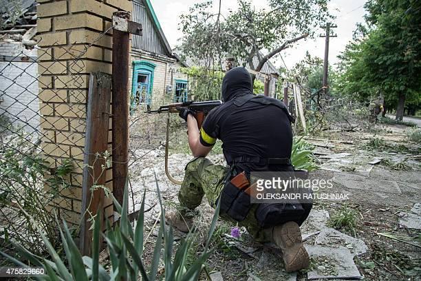 A Ukrainian service man holds a gun during fightings in the Ukrainian city of Mariinka in the region of Donetsk on June 4 2015 Ukrainian President...