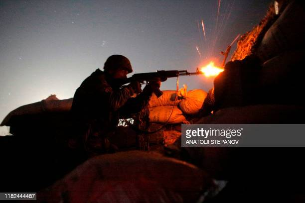 Ukrainian serviceman fires at Russiabacked separatists during night combat on the front line near Novolugansk in the Donetsk region on November 14...