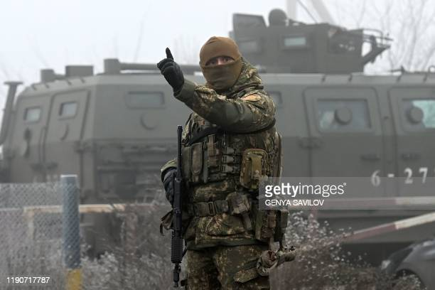 A Ukrainian serviceman gestures while standing guard in the settlement of Odradivka near the Mayorsk checkpoint prior to a prisoner exchange between...