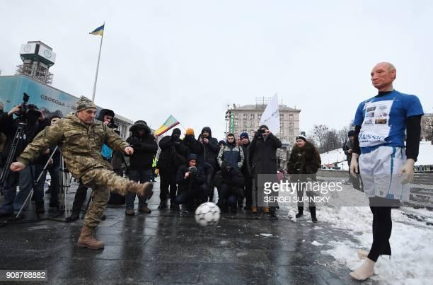 A Ukrainian serviceman kicks a ball at a mannequin depicting Russian President Vladimir Putin dressed in a football uniform during the 'Stop Putin...