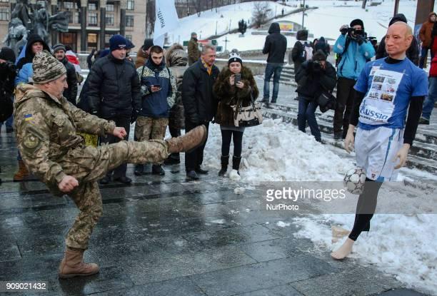 A Ukrainian serviceman kicks a ball at a mannequin depicting Russian President Vladimir Putin dressed in a football uniform during the quotStop Putin...