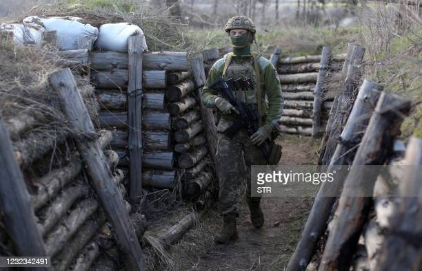 Ukrainian serviceman patrols along a trench in Schastya, Lugansk region, near the frontline with Russia backed separatists on April 16, 2021. - On...