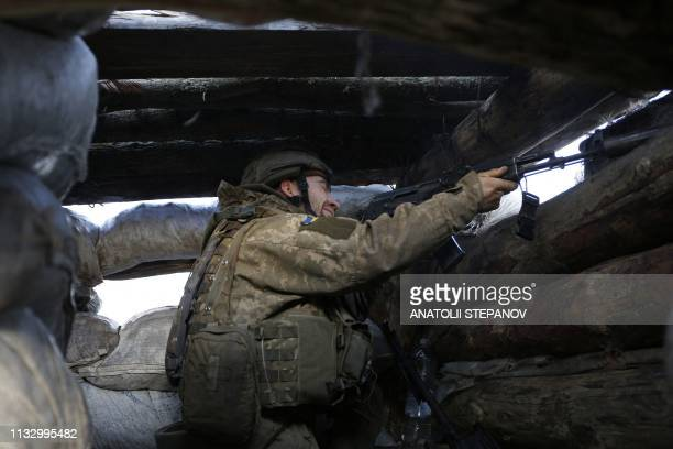 Ukrainian serviceman shoots from the dugout on the front line with Russianbacked separatists near Zhelobok village Lugansk region on March 25 2019...