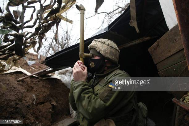 Ukrainian serviceman stands guard at a position on the frontline with Russia backed separatists near small city of Marinka, Donetsk region on April...