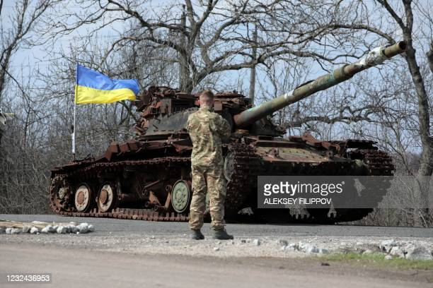 Ukrainian serviceman stands next to a Ukrainian tank destroyed in 2014 by Russia backed separatists, on the front line near the small town of Pisky,...