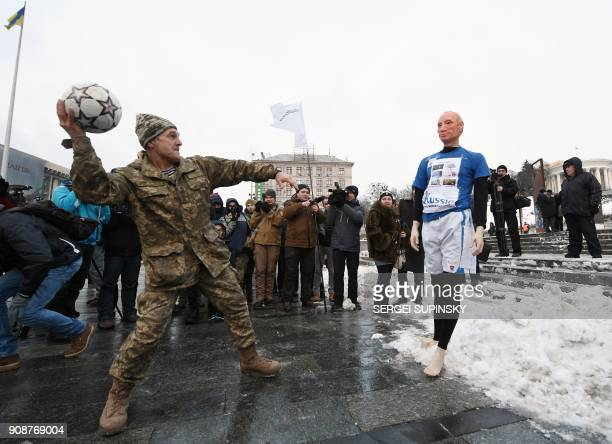 A Ukrainian serviceman throws a ball at a mannequin depicting Russian President Vladimir Putin dressed in a football uniform during the 'Stop Putin...