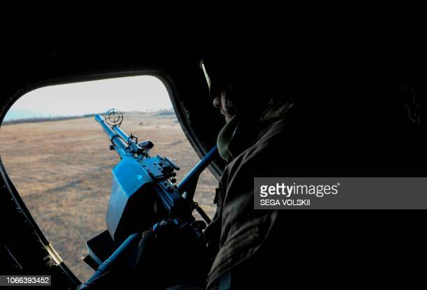 A Ukrainian serviceman with a machine gun secures the area from a helicopter during military drills near Urzuf village not far from the city of...