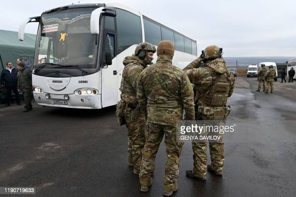 Ukrainian servicemen guard an area during a prisoner exchange between Ukraine and proRussian rebels near the Mayorsk checkpoint on December 29 2019