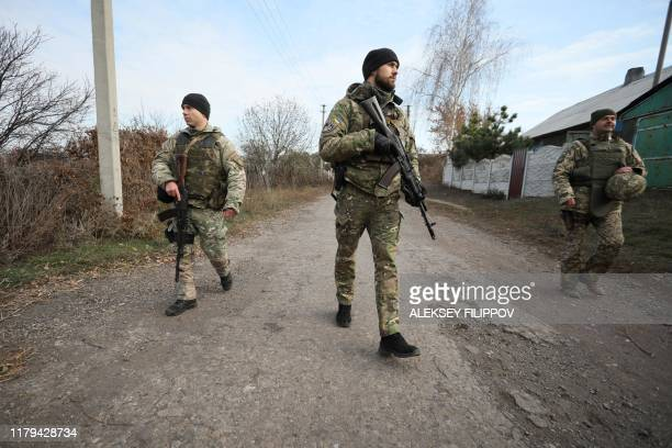 Ukrainian servicemen patrol in the streets of the village of Katerynivka, in the Lugansk region on November 2 after their withdrawal. - Ukrainian...