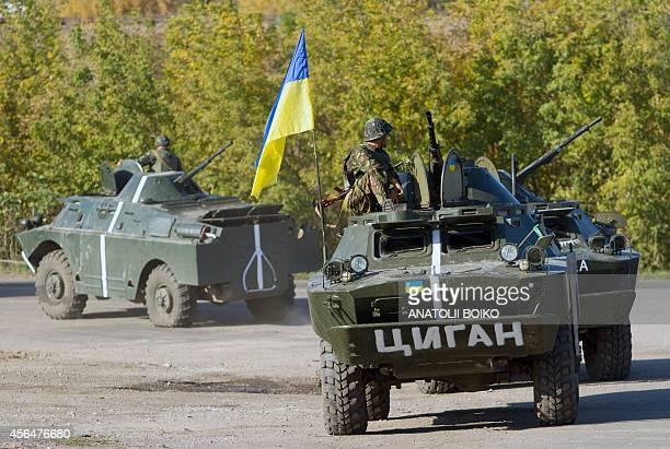 Ukrainian servicemen patrol on an armoured personnel carrier on a road near Debaltseve in Donetsk region on October 1 2014 Ten civilians died in...