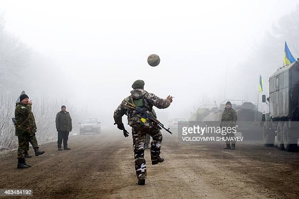 Ukrainian servicemen play football on a road at Svitlodarsk approaching Debaltseve on February 15 2015 A ceasefire in Ukraine was cautiously observed...