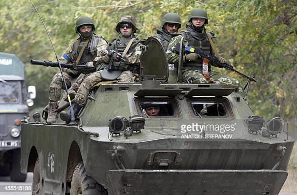 Ukrainian servicemen sit atop of an armored personnel carrier as they patrol in Donetsk region on September 16 2014 The Ukrainian and European...