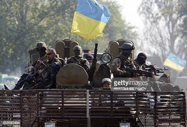 Ukrainian servicemen sit atop of an Armoured Personnel Carrier during a patrol in Donetsk region on September 15 2014 USled military exercises began...