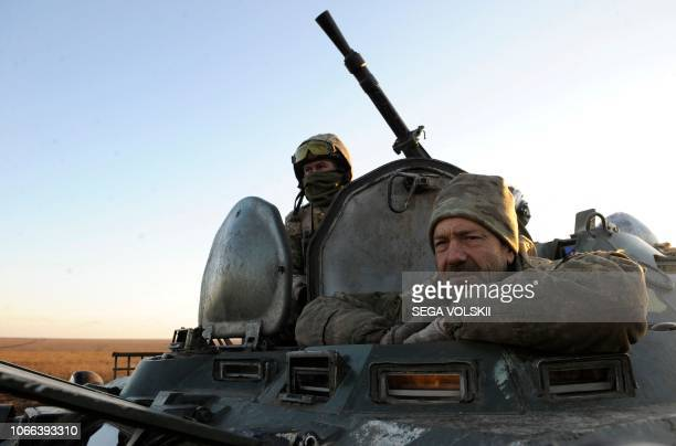 Ukrainian servicemen sit on an APC during military drills near Urzuf village not far from the city of Mariupol eastern Ukraine on November 29 2018...