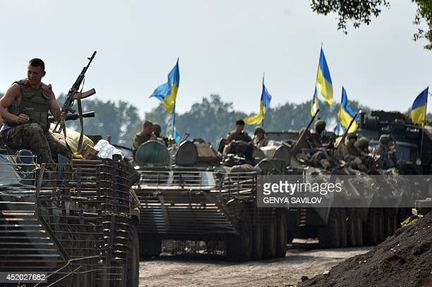 Ukrainian servicemen sitting atop armored personnel carriers travel near the eastern Ukrainian city of Slavyansk on July 11 2014 Ukraine's military...