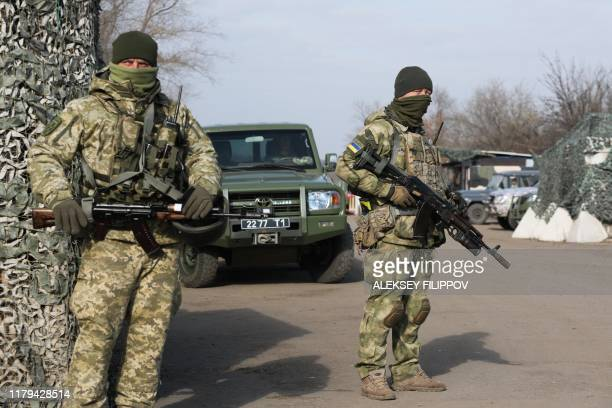 Ukrainian servicemen stand guard at a checkpoint situated on the new positions not far from the town of Zolote, in the Lugansk region on November 2...