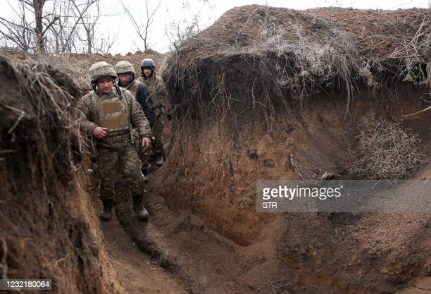 Ukrainian servicemen walk in a trench as they stand at their post on the frontline with Russia backed separatists near the town of Zolote, in the...