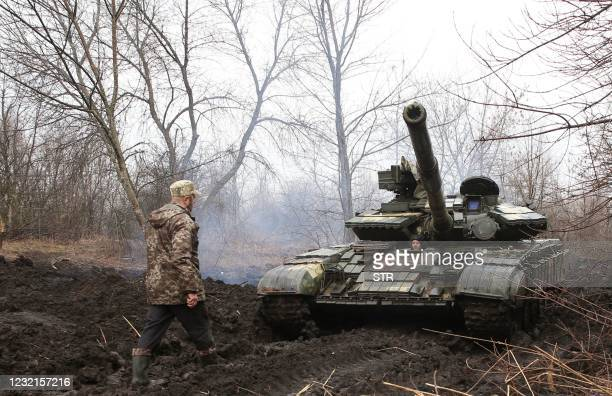 Ukrainian servicemen work on their tank close to the front line with Russian-backed separatists near Lysychansk, Lugansk region on April 7, 2021. -...