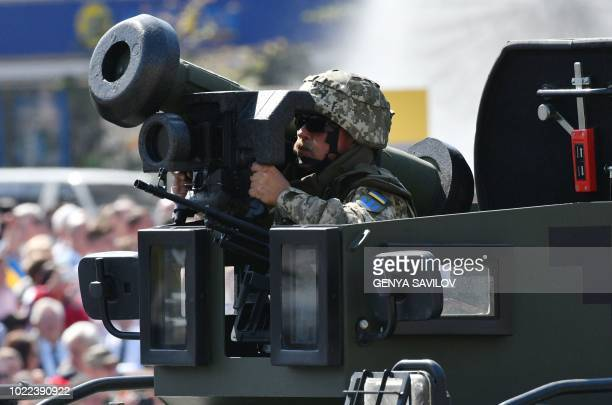 Ukrainian serviseman rides atop of an APC with Javelin anti-tank missiles during a military parade in Kiev on August 24, 2018 to celebrate the...