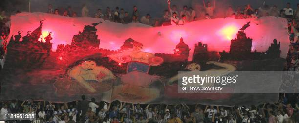 Ukrainian soccer fans hold up a giant banner featuring Cossacks during the Champion League soccer match between Dynamo Kiev vs Spartak Moscow in Kiev...