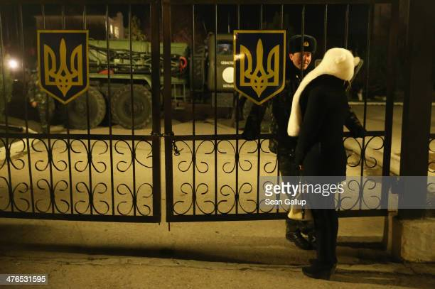 Ukrainian soldier and a young woman chat at the main gate of the Belbek military base while anticipating a possible Russian attack as a truck blocks...