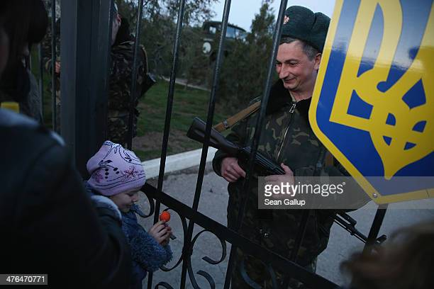 Ukrainian soldier at the Belbek military base talks with family members, including his daughter, through the gates of the base entrance on March 3,...
