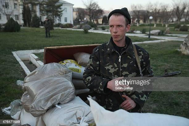 Ukrainian soldier clutches his Kalashnikov machine gun at a sandbag position at the Belbek military base on March 3, 2014 in Lubimovka, Ukraine....