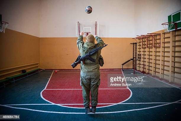 Ukrainian soldier from the Azov Battalion plays basketball in a school gymnasium before being sent back to the front lines on March 9, 2015 in...