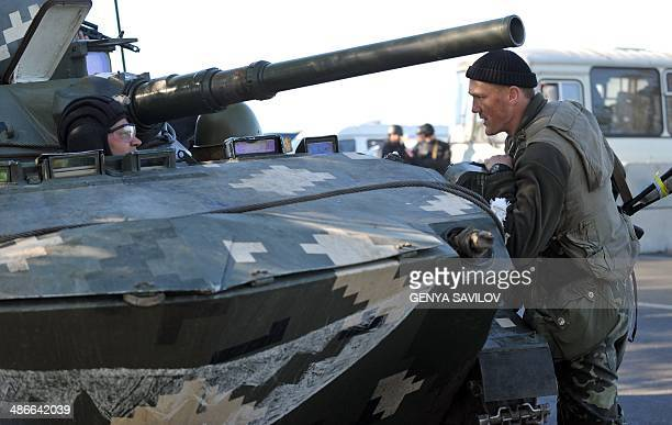 A Ukrainian soldier in a tank speaks with another at their newly erected checkpoint near the eastern Ukrainain city of Slavyansk on April 25 2014...