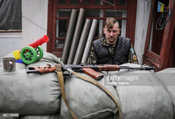 Ukrainian soldier in front of a house with his gun in the village of Peski Donetsk region controlled by Ukrainian forces on November 19 2014