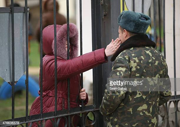 Ukrainian soldier inside the Belbek military base gets an affectionate pet from a woman who was among approximately two dozen who spent the night...