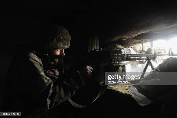 A Ukrainian soldier looks through the scope of his gun in a shelter located in the front line with Russiabacked separatists in the small city of...